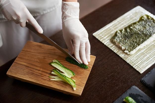 Vergrote weergave van proces ter voorbereiding van heerlijke rollende sushi in restaurant. vrouwelijke handen in wegwerphandschoenen komkommer snijden op een houten bord.