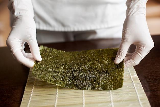 Vergrote weergave van proces ter voorbereiding van rollende sushi. de handen van de chef houden een vel nori vast en beginnen te koken