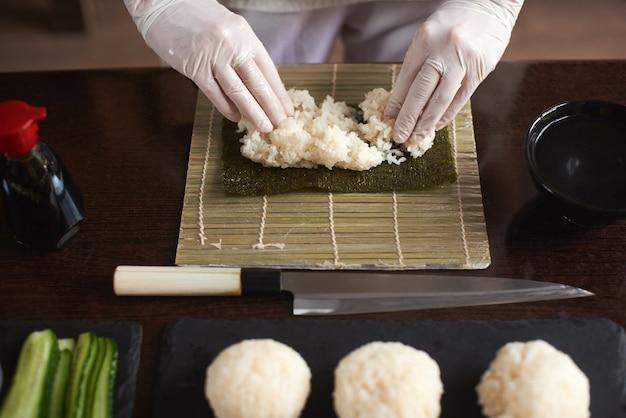 Vergrote weergave van proces ter voorbereiding van rollende sushi. nori en witte rijst. de handen van de chef-kok raken rijst aan. chef begint sushi te koken