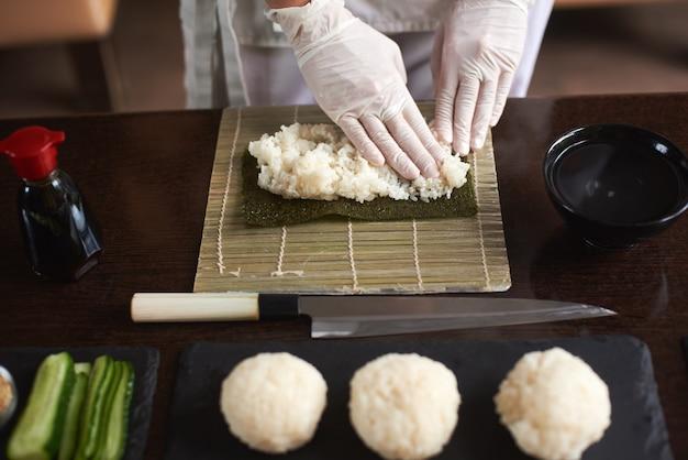 Vergrote weergave van proces ter voorbereiding van rollende sushi. nori en witte rijst. de vrouwelijke handen van de chef raken rijst aan. chef begint sushi te koken