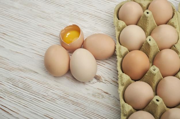Vergrote weergave van rauwe kippeneieren in eierdoos op houten
