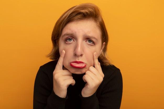 Vergrote weergave van trieste jonge blonde vrouw die naar de voorkant kijkt en oogleden naar beneden trekt die op een oranje muur zijn geïsoleerd