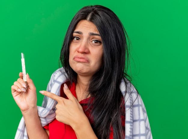 Vergrote weergave van trieste jonge zieke vrouw gewikkeld in geruite bedrijf en wijzend op thermometer kijken voorzijde geïsoleerd op groene muur