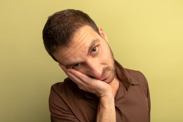 Vergrote weergave van verveelde jonge blanke man hand zetten gezicht kijken camera geïsoleerd op olijfgroene achtergrond