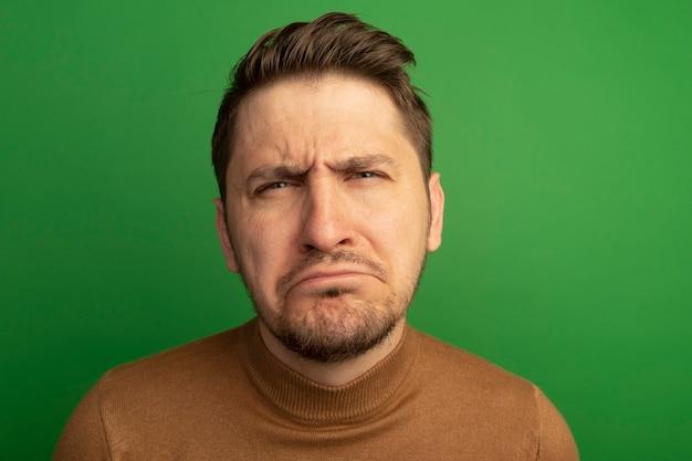 Vergrote weergave van verwarde jonge blonde knappe man die geïsoleerd op groene muur kijkt