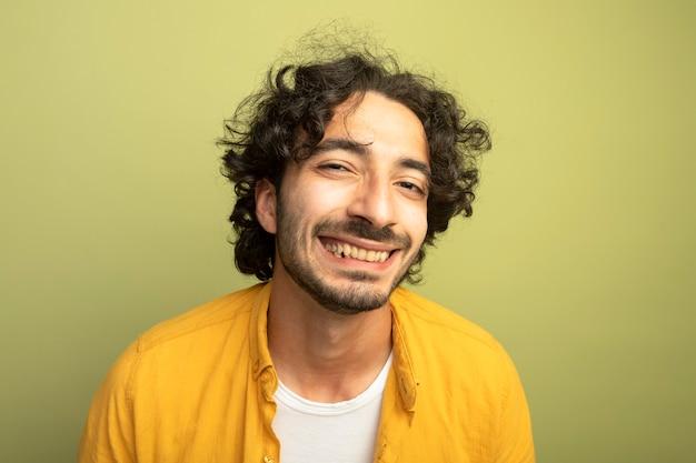 Vergrote weergave van vrolijke jonge knappe man kijken voorzijde geïsoleerd op olijfgroene muur