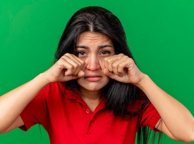 Vergrote weergave van zwakke jonge zieke vrouw aanraken gezicht met vuisten kijken voorzijde geïsoleerd op groene muur
