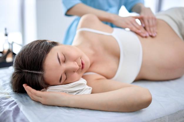 Vergrote weergave van zwangere vrouw die massage op buik krijgt van mijn vrouwelijke masseur, genietend met gesloten ogen, rust tijdens de spabehandeling