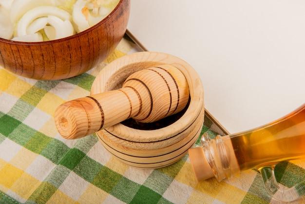 Vergrote weergave van zwarte peper zaden in knoflook crusher met gesmolten boter en kom gesneden ui met notitieblok op geruite doek achtergrond