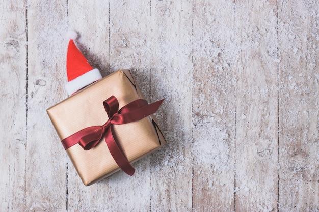 Verguld cadeau met een rode strik en een kerstmuts