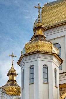 Vergulde koepels van orthodox-christelijke kerk schijnen op de blauwe hemelachtergrond