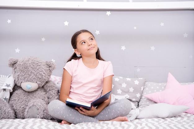 Verhaal dat tot de verbeelding spreekt. klein meisje lezen en voorstellen. leuke dromer met boek en speelgoed. kinderen verbeelding en fantasie. lezen voedt de verbeelding. inspirerende kinderverbeelding.
