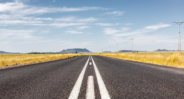 Verharde rechte weg door een droog landschap in zuid-afrika onder een bewolkte hemel