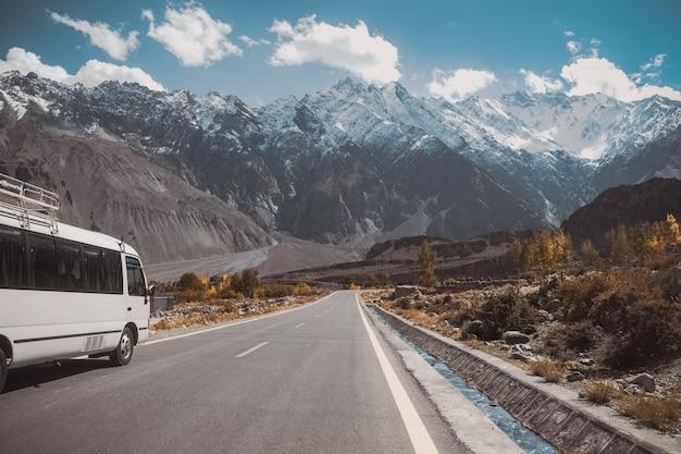 Verharde weg in passu met uitzicht op besneeuwde bergketen, karakoram snelweg pakistan.