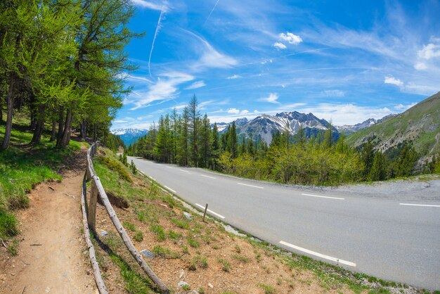 Verharde weg met twee rijstroken in schilderachtig alpien landschap en humeurige hemel, fisheyemening. zomeravontuur en roadtrip in col d'izoard, frankrijk.