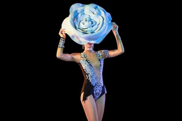 Verheugd. jonge danseres met enorme bloemenhoed in neonlicht op zwarte muur. sierlijk model, vrouw dansen, poseren. concept van carnaval, schoonheid, beweging, bloei, lentemode.