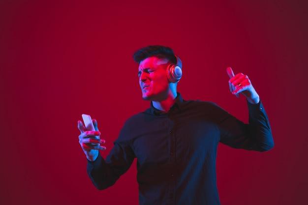 Verheugd naar muziek luisteren. portret van een blanke jongeman geïsoleerd op rode muur in neonlicht. mooi mannelijk model. concept van menselijke emoties, gezichtsuitdrukking, jeugdcultuur.