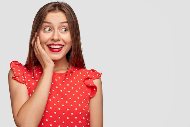Verheugd vrouw met rode lippenstift poseren tegen de witte muur
