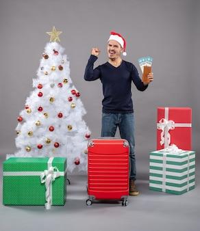 Verheugde man met koffer die zijn reistickets op grijs hield