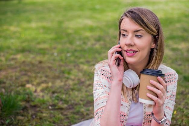 Verheugde vrouw die in de buitenlucht in gesprek zit. meisje met koffie drinken praten op smartphone. vrouw in koptelefoon luisteren muziek in de natuur