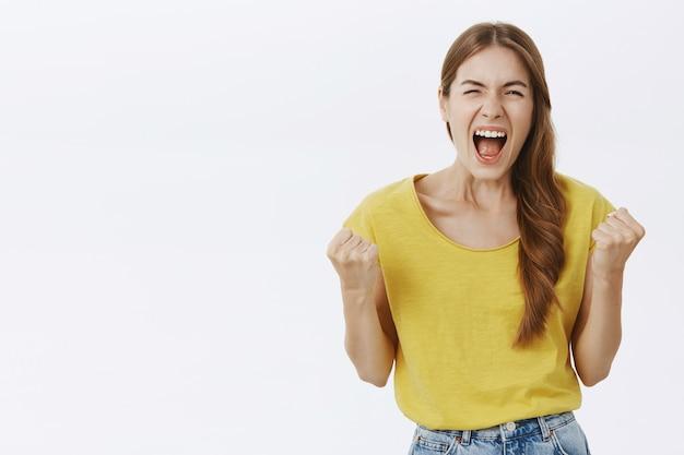 Verheugend gelukkig jong meisje dat wint, overwinning viert, ja schreeuwt en triomfeert
