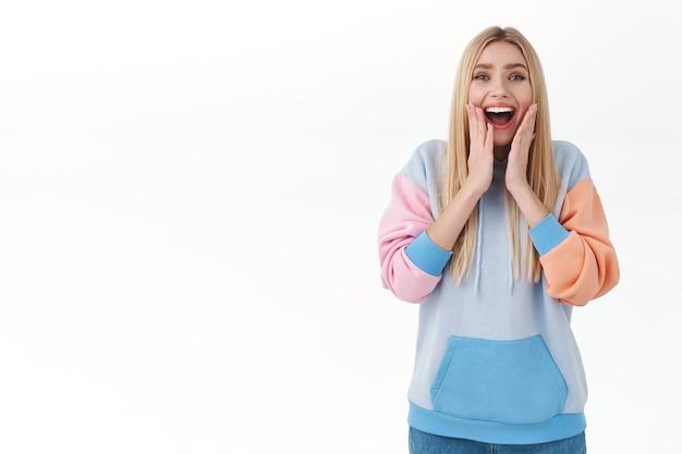 Verheugende, gelukkige vrouwelijke blonde blanke vrouw, zuchtend en glimlachend gelukkig