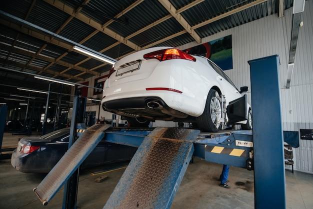 Verhoogde auto op de lift in het tankstation om het uitlaatsysteem te diagnosticeren. tankstation