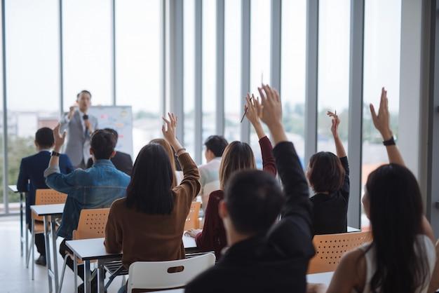 Verhoogde handen en armen van een grote groep in seminarieklassen om eens te worden met de spreker op de conferentieruimte