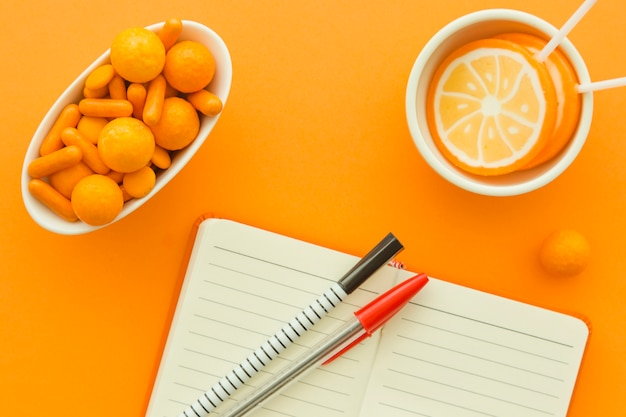 Verhoogde mening van blocnote, pen dichtbij suikergoed en lollys op oranje achtergrond