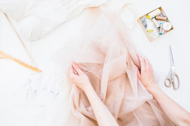 Verhoogde mening van de hand van de ontwerper met textiel en naaiende toebehoren op werkbank