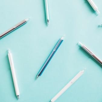 Verhoogde mening van diverse pennen op turkoois gekleurde achtergrond