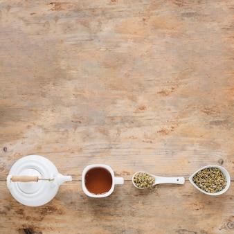 Verhoogde mening van droge chinese chrysantenbloemen; theepot en citroenthee gerangschikt in een rij op tafel