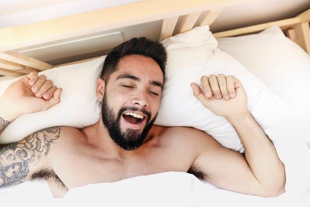 Verhoogde mening van een jonge man die in de ochtend ontwaakt