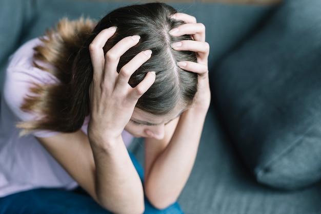 Verhoogde mening van een vrouw die aan hoofdpijn lijdt