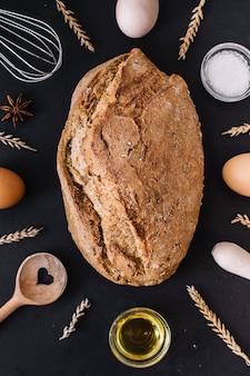 Verhoogde mening van heerlijk brood met diverse bakselingrediënten en werktuigen op zwarte oppervlakte