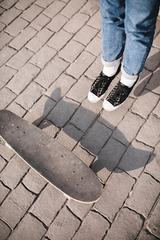 Verhoogde mening van het been van skateboarder en skateboard op bestrating