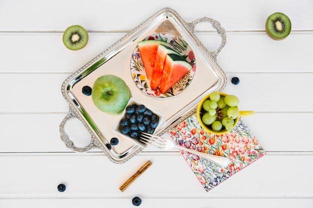 Verhoogde mening van kiwi en druiven dichtbij bosbessen; gesneden watermeloen en appel op dienblad