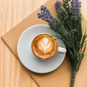 Verhoogde mening van koffie latte, notitieboekje en lavendelbloem