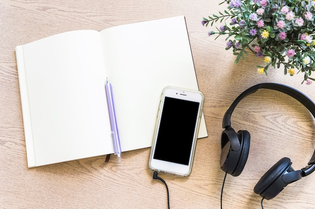 Verhoogde mening van leeg boek met pen; mobiele telefoon en oortelefoon op houten tafel