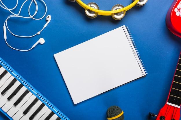 Verhoogde mening van lege spiraalvormige blocnote die met oortelefoon wordt omringd; gitaar; microfoon; pianotoetsenbord en tamboerijn over blauwe achtergrond