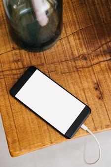 Verhoogde mening van smartphone op houten bureau