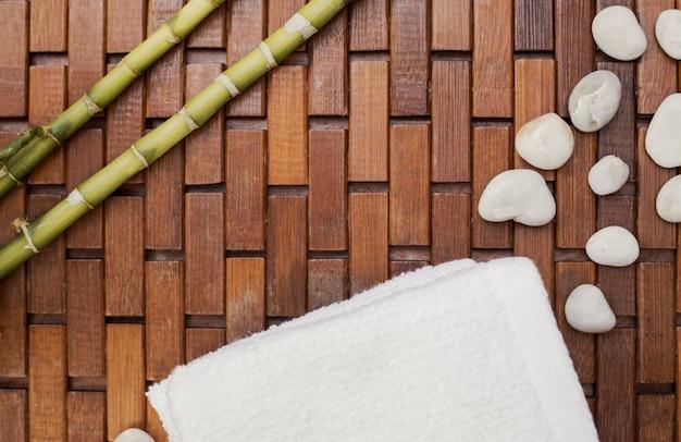 Verhoogde weergave van bamboe plant; witte handdoek en kiezels op houten vloer