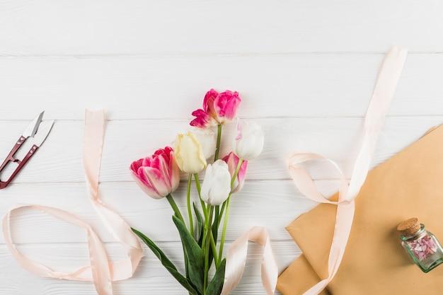Verhoogde weergave van bruin papier; tulp bloemen; lint en cutter tegen witte bureau