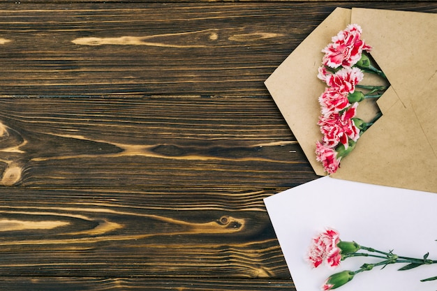 Verhoogde weergave van carnation bloemen omhullen op bruine tafel