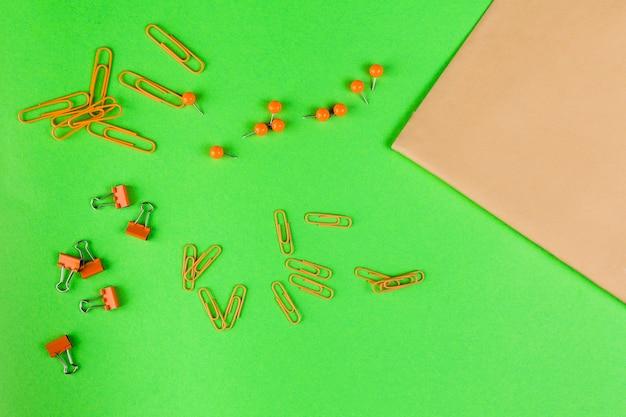 Verhoogde weergave van de punaise; paperclip en bulldog clip met bruin papier op heldergroene achtergrond