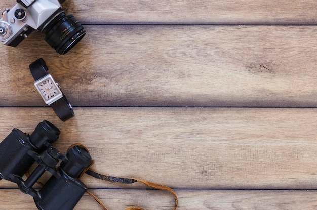 Verhoogde weergave van een verrekijker; polshorloge en camera op houten achtergrond