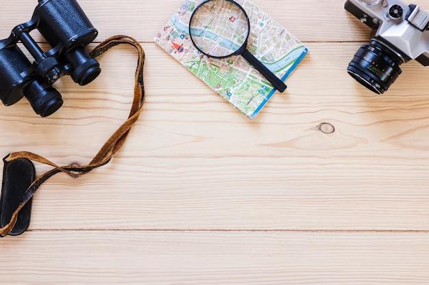 Verhoogde weergave van een verrekijker; vergrootglas; kaart en camera op houten oppervlak