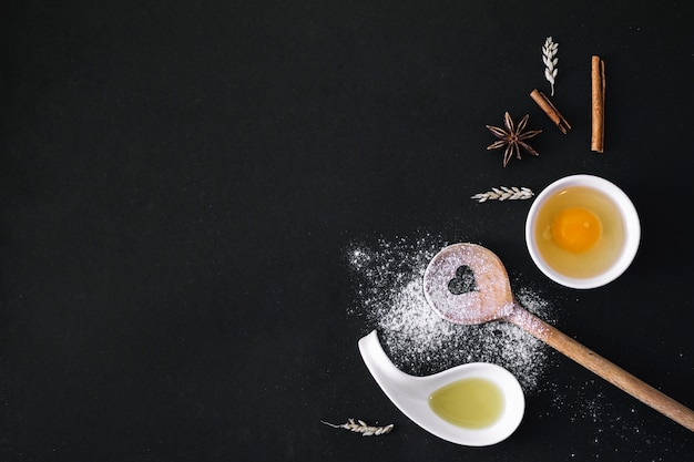 Verhoogde weergave van ei; specerijen; graan; hartvormige lepel; bloem en olie op zwart oppervlak