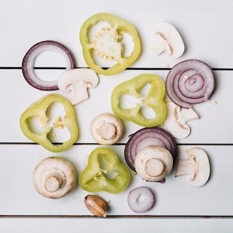Verhoogde weergave van gesneden groene paprika; champignons en uien op houten plank