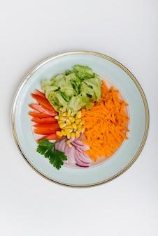 Verhoogde weergave van gesneden wortel; sla; tomaat; maïs; ui en parley op de plaat